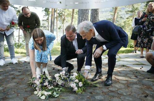 Leader of AUF in Norway, Astrid Hoem, Prime Minister of Sweden Stefan Loefven and leader of the Norwegian Labor Party Jonas Gahr Store lay flowers at a memorial for the victims of the Utoya massacre.