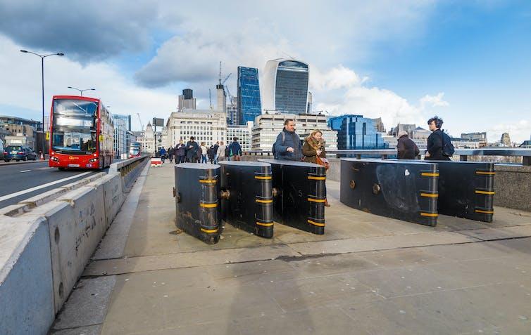 Anti-vehicle bollards on London Bridge, with skyscrapers behind