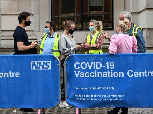 People queuing outside of a UK COVID vaccine centre