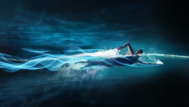 Person swimming, leaving streaks of light in path