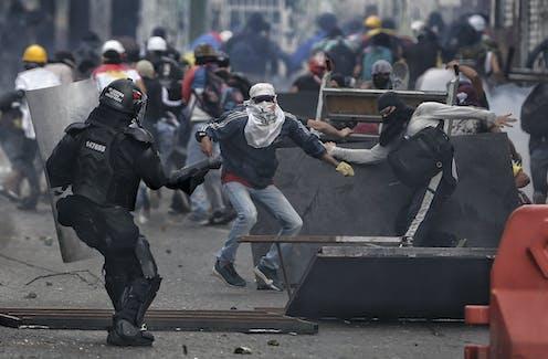 Altercation entre des policiers et manifestants dans la rue.