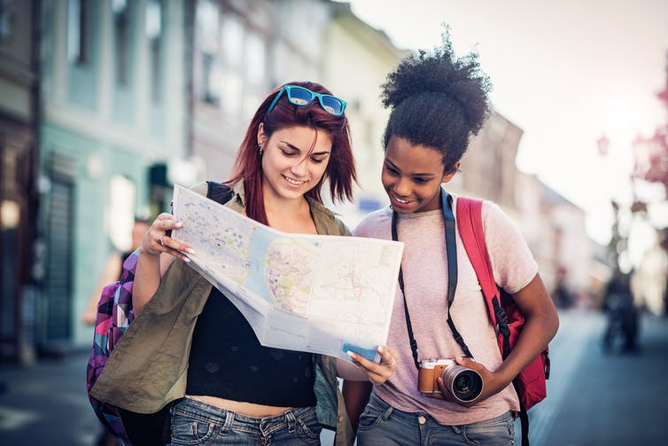 Two teenagers look at a map together while walking in a street