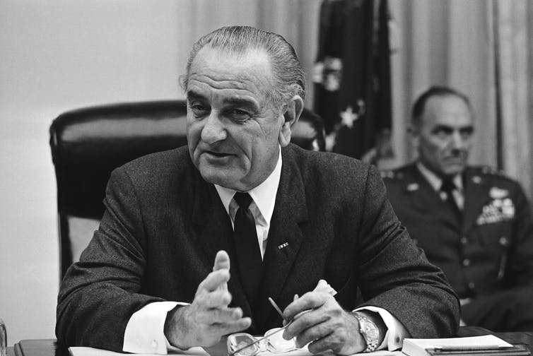 President Lyndon Johnson, sitting at his desk in a suit, tie and white shirt.