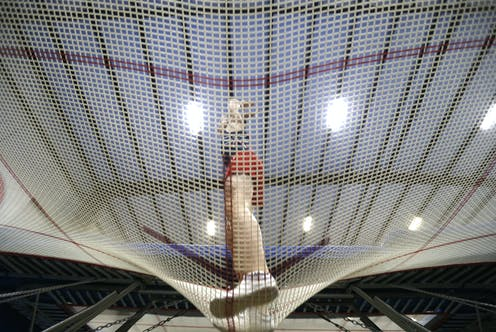 A male gymnast is seen through the holes of a trampoline as he bounces on it.
