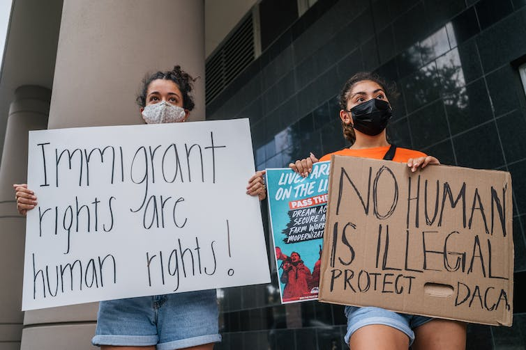 Two young women wearing face masks holding signs protesting outside a courthouse