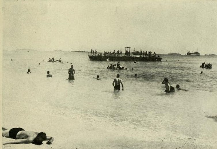 People swimming in a lagoon, with some sunbathing on a beach, ships in the background.