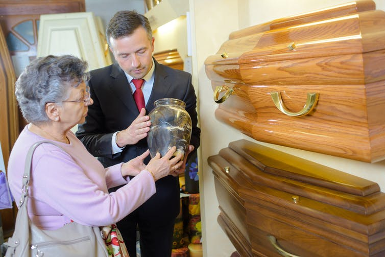 A woman in a funeral parlour choosing a coffin discussing costs with a salesman.