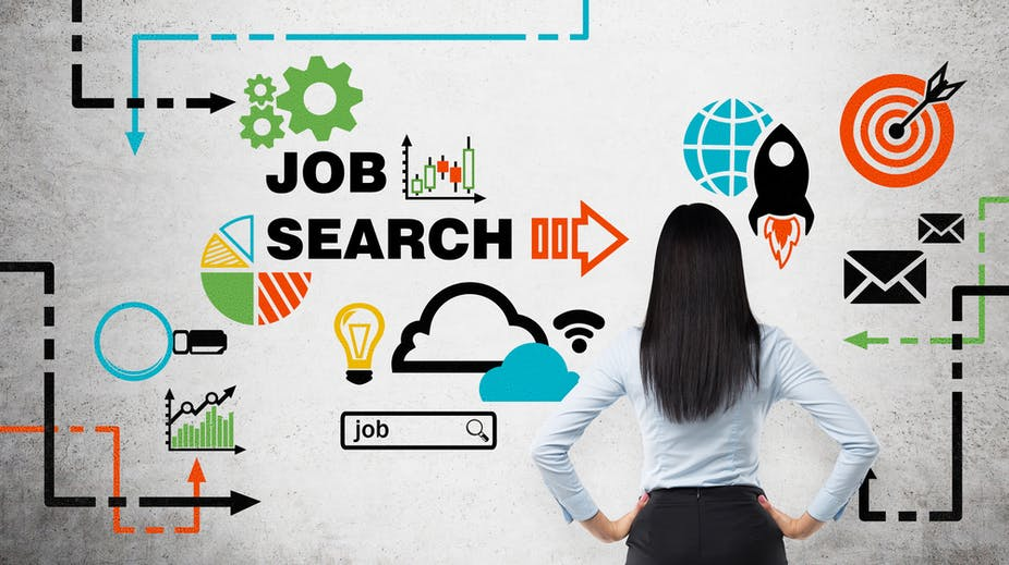 Rear view of a young woman who is looking at the wall with colourful icons about job vacancies.