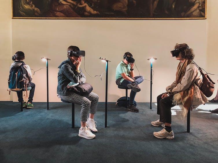 Groupe de personnes expérimentant la réalité virtuelle assise, dans une salle de musée.