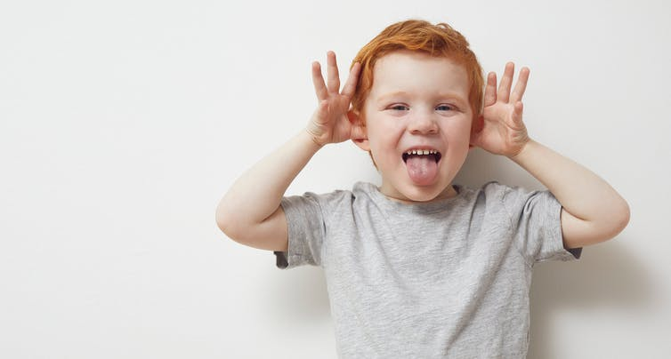 Young boy with his thumbs in his ears, waving hands and sticking his tongue out.