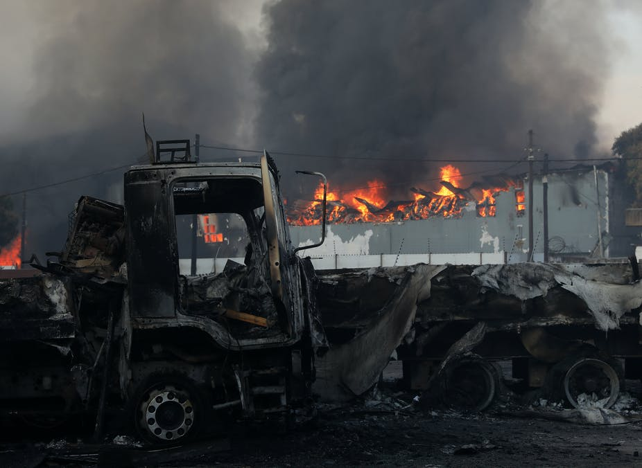 A business building is engulfed in flames next to burnt trucks.