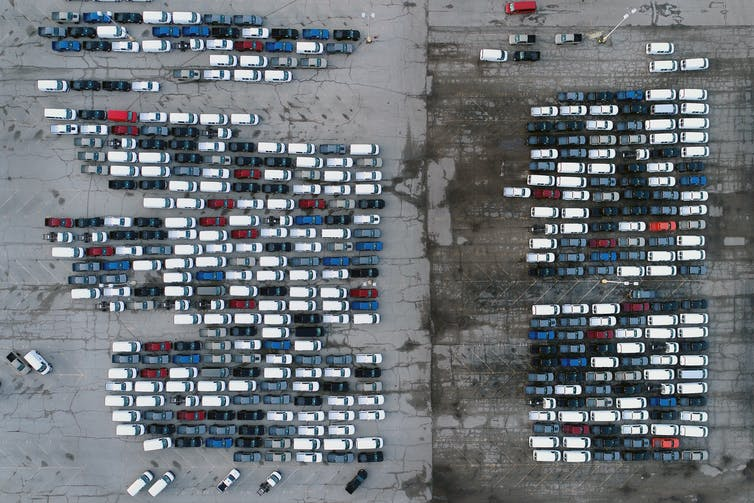 an aerial photo of mid-sized pickup trucks and full-size vans in a parking lot