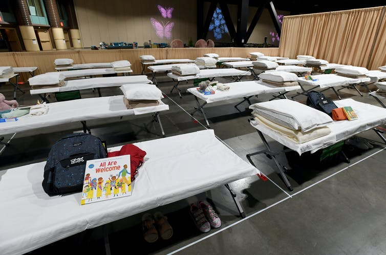 Cots lined up in a large space, some with backpacks and children's books on them