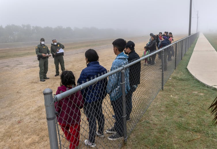 Two border patrol agents holding papers look at people standing on a dirt road in two separate groups along a fence line