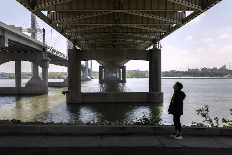 Girl stands under a bridge over a river
