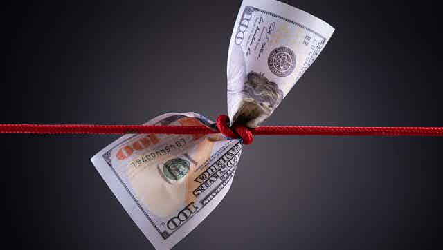 A $100 bill with a red cord tied around the middle.