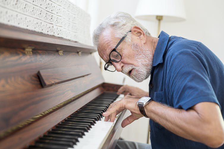 older man leans in and looks at his hands on the piano keyboard