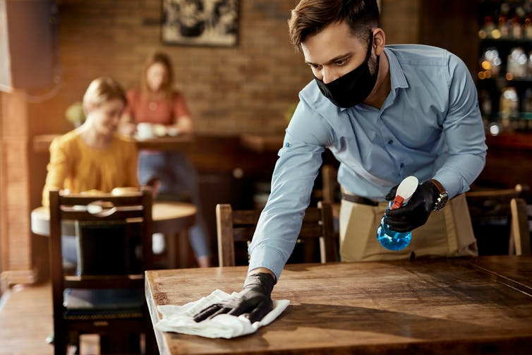 A waiter wipes down a table in a cafe.