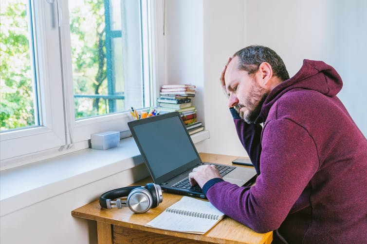 Frustrated looking man sits at laptop next to window