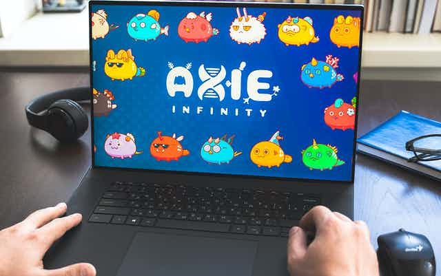 A laptop showing Axie Infinity with someone's hands on the keyboard