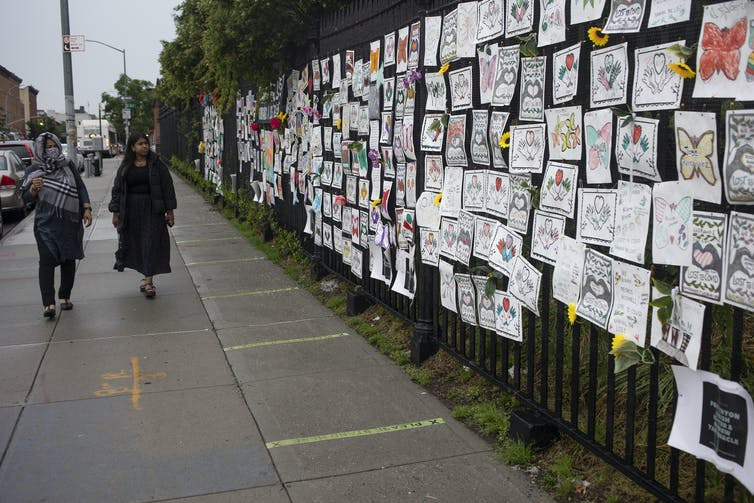 A fence alongside Greenwood Cemetery in Brooklyn, New York covered with memorial art for those who died of COVID-19.