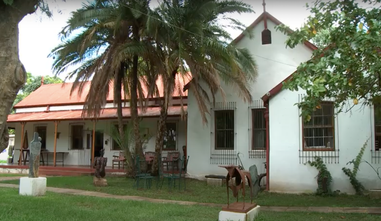 A house with palm tree, old red zinc roof and old facade, church-like on green lawns