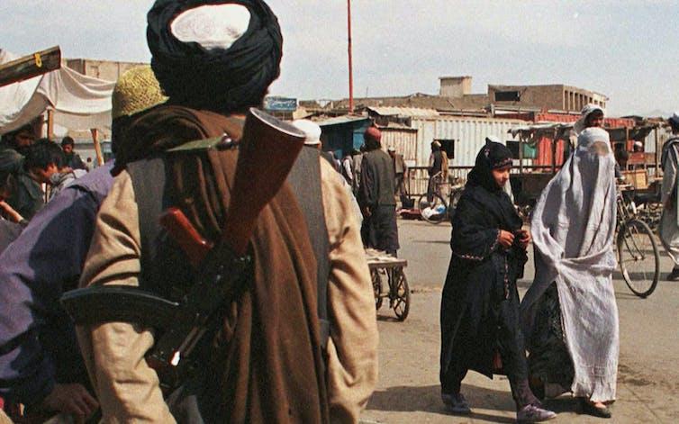 Dos mujeres afganas con diferentes estilos de burka pasan junto a un soldado de la milicia talibán fundamentalista armado.