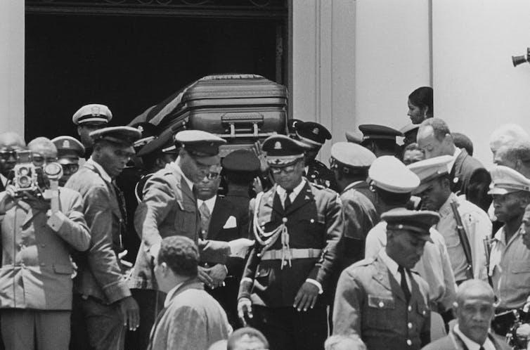 Government officials carry a casket.