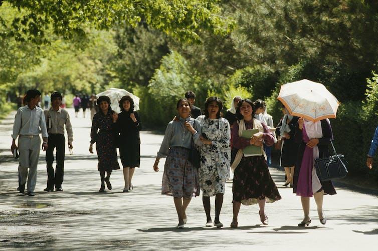 Hombres y mujeres jóvenes pasean por el parque de Kabul.