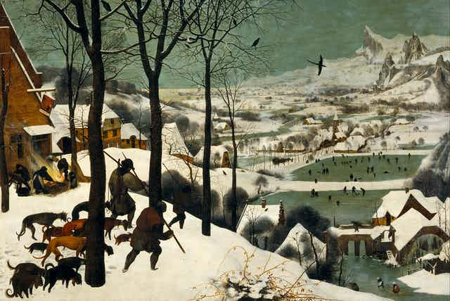 Historic painting of hunters with dogs walking over a snowy hillside toward a town where people are skating on a frozen river
