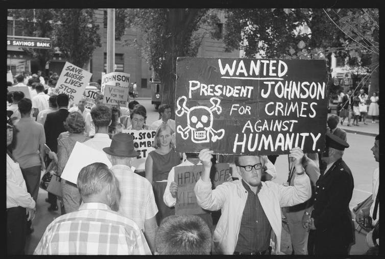 Sign reads 'wanted: President Johnson for crimes against humanity'