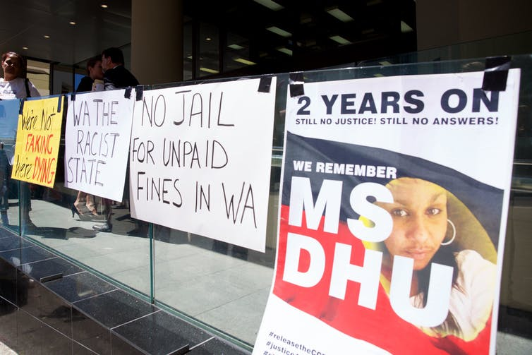 Signs put up by supporter of Ms Dhu outside the coroner's court in Perth.