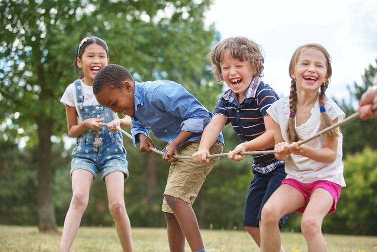 A group of children playing a game of tug-of-war in a park.