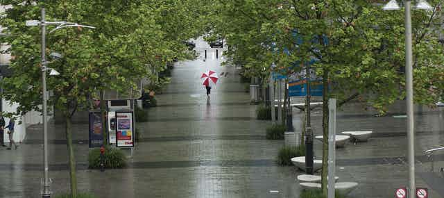 Person walking down a rainy street with red and white umbrella