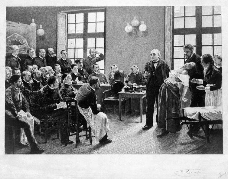 An etching of a man holding on to a woman who has fainted as he addresses a room full of male students
