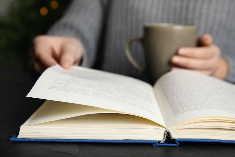 Person reading book with a cup of tea.
