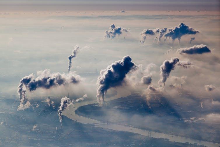 Des cheminées d'usine émettant des nuages de pollution sur une ligne d'horizon brumeuse.