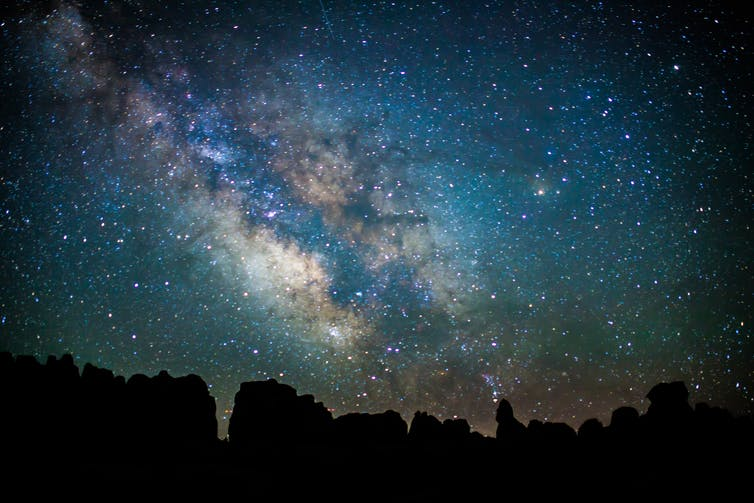 A nighttime photograph taken at Utah's Canyonlands National Park, looking skyward and revealing thousands of stars in the Milky Way.