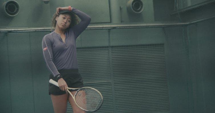 Osaka holding a tennis racquet.