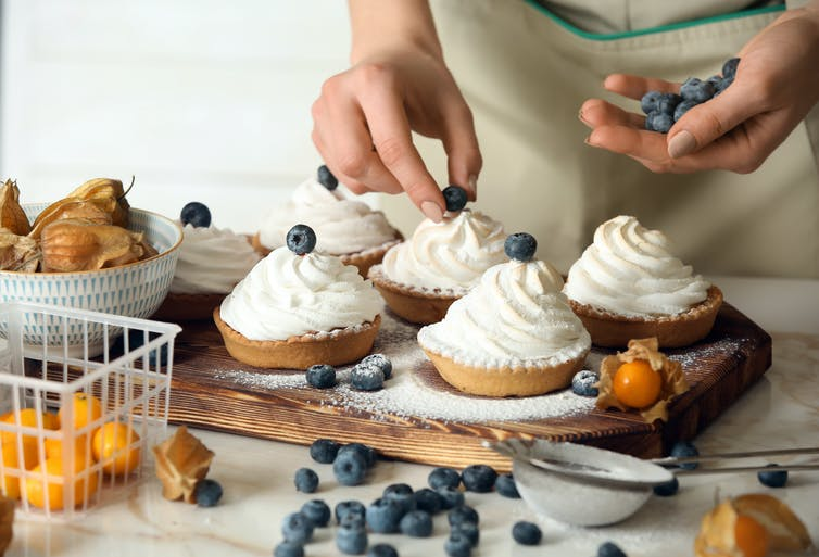 A person preparing tarts with whipped cream on top.