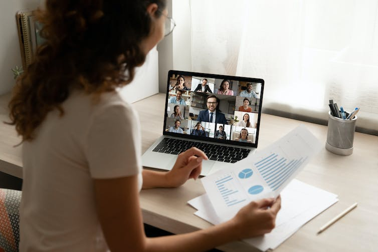 Young woman at a desk chats to a group in an online meeting via her laptop