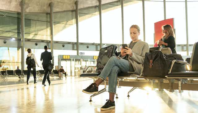 Woman with luggage sits at airport terminal looking at her phone.