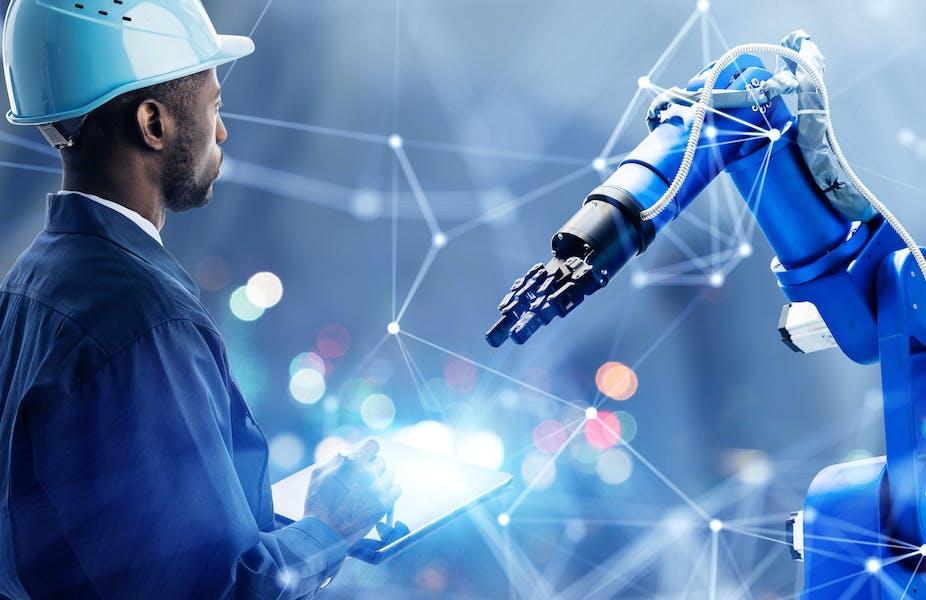 Operativo con casco inspeccionando un brazo robótico