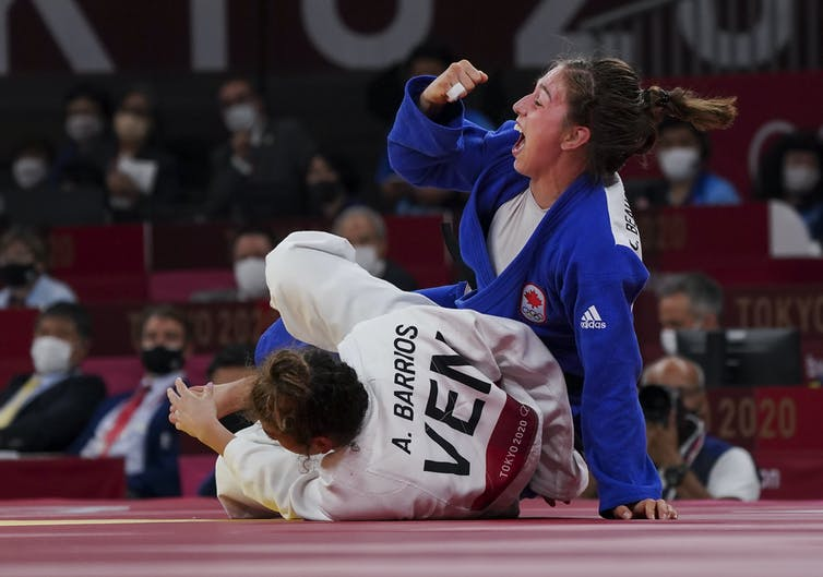 Catherine Beauchemin-Pinard lève son poing droit en signe de victoire alors que son adversaire est au tapis