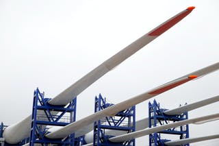 Tres palas de aerogenerador dispuestas sobre andamio.