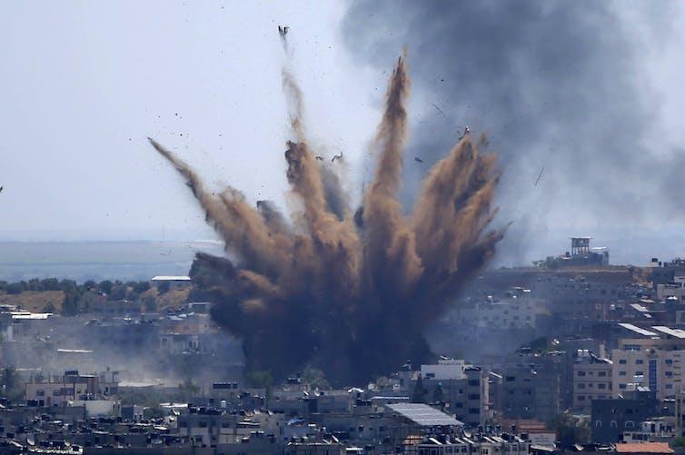 Une explosion de fumée et de débris s'élève d'un bâtiment qui vient d'être touché par une frappe de missile israélien dans une zone densément peuplée de la ville de Gaza