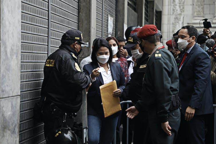 Fujimori passes through security holding a manila envelope in her hand