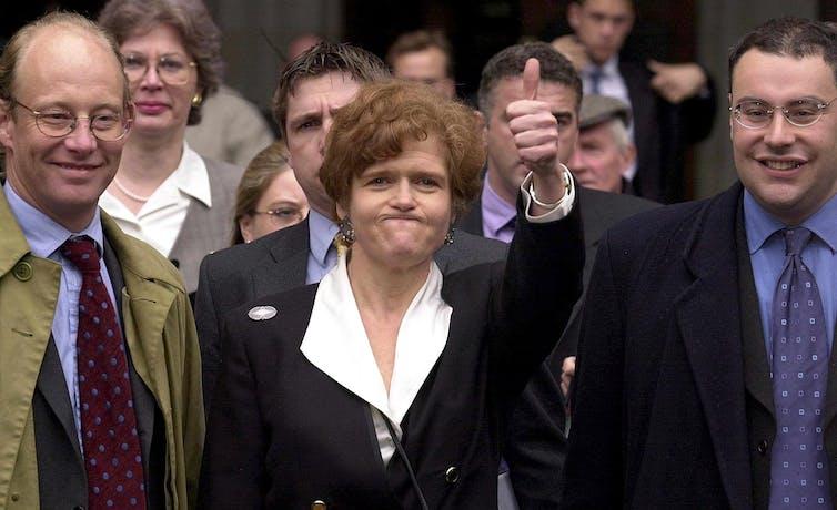 Une femme élégamment vêtue lève le pouce, flanquée de deux hommes souriants.