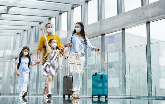 Family of four walk through the airport with masks on