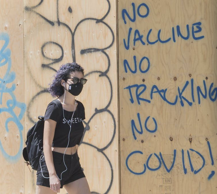 A woman wears a face mask as she passes by anti-vaccine graffiti